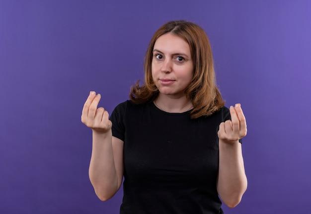 Jonge toevallige vrouw die geldgebaar op geïsoleerde purpere muur met exemplaarruimte doet
