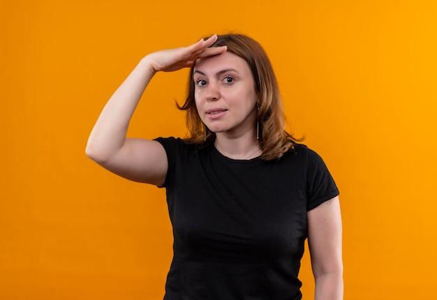 Jonge toevallige vrouw die hand op voorhoofd zet en op geïsoleerde oranje muur kijkt