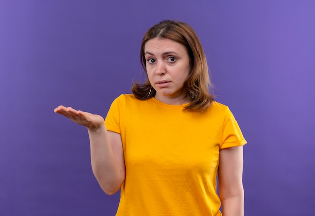 Jonge toevallige vrouw die lege hand op geïsoleerde purpere muur toont