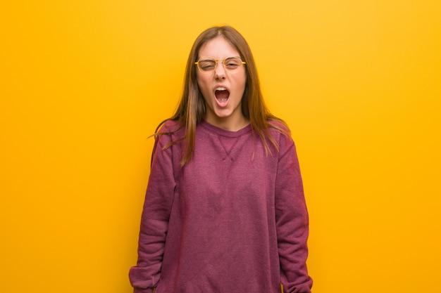 Jonge toevallige vrouw die zeer boos en agressief gilt