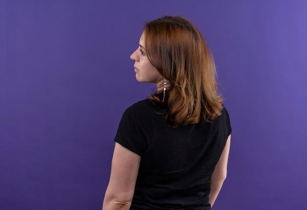Jonge toevallige vrouw die zich binnen achter mening bevindt die naar linkerkant op geïsoleerde purpere muur met exemplaarruimte kijkt
