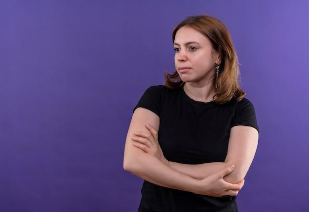 Jonge toevallige vrouw die zich met gesloten houding bevindt en naar linkerkant op geïsoleerde purpere muur met exemplaarruimte kijkt