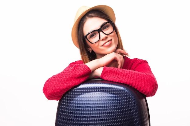 Jonge toevallige vrouw die zich met reiskoffer bevindt - die op witte muur wordt geïsoleerd. roeping concept