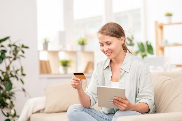 Jonge toevallige vrouwelijke shopper die persoonlijke gegevens op plastic kaart bekijkt terwijl voor online orde gaat betalen