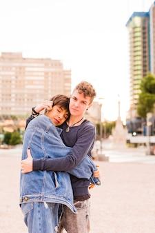 Jonge tomboy lesbisch koppel niet-binaire transgender en een spaanse vrouw knuffel