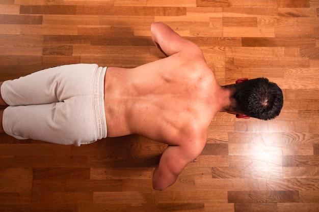 Jonge topless blanke man doet push-ups thuis vanuit een zenitale hoek