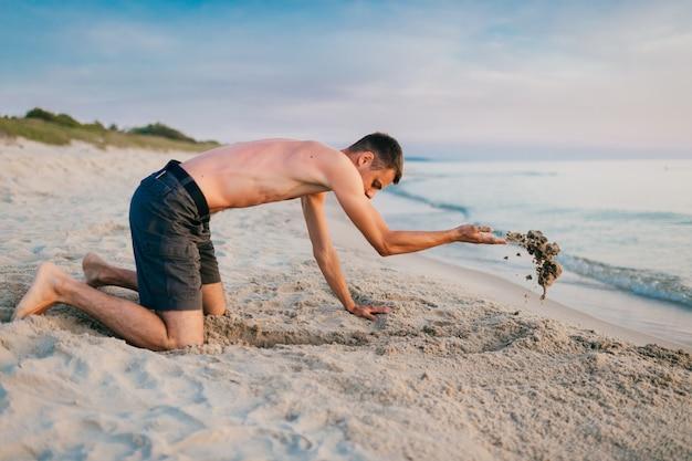Jonge topless blootvoetse mens in borrels die zich op knieën bevinden en kuil graven door handen op strand voorbij overzees in de zomeravond.