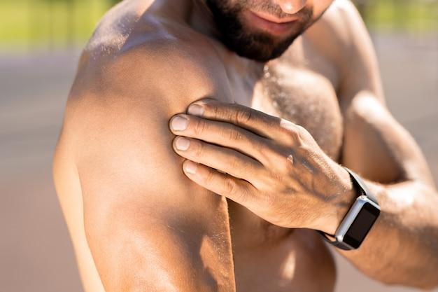 Jonge topless gespierde atleet met smartwatch zijn biceps aan te raken tijdens het trainen buiten