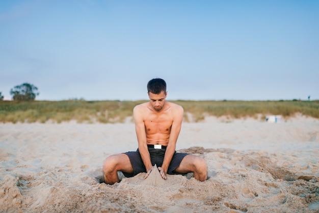 Jonge topless mensenzitting op strand voorbij overzees met benen binnen gehelen in zand en beeldhouwende cijfers van zand door handen zoals kind.
