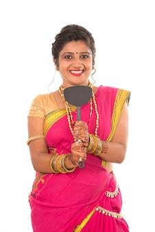 Jonge traditionele indiase meisje keuken gebruiksvoorwerp op wit te houden