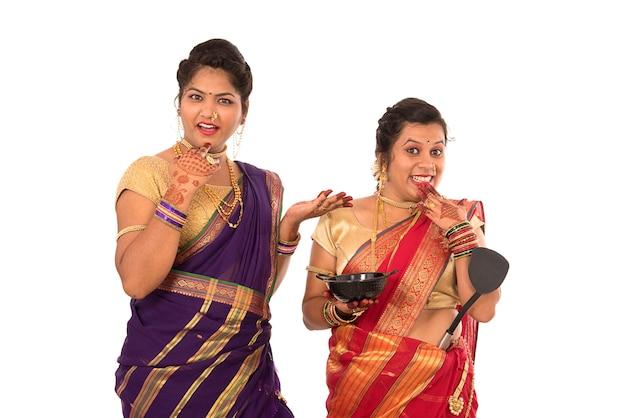 Jonge traditionele indiase meisjes die keukengerei op wit houden