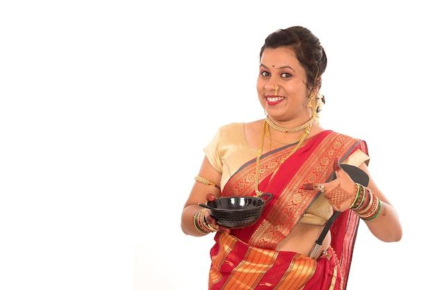 Jonge traditionele indiase vrouw met keukengerei