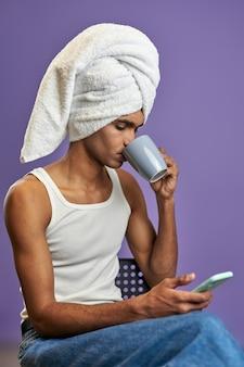 Jonge transgender man in badjas handdoek op hoofd kijkt in mobiel scherm en drinkt koffie