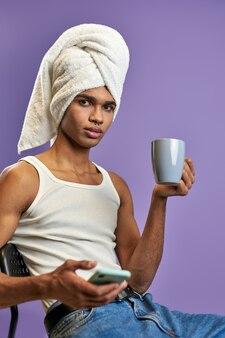 Jonge transgender man in handdoek op hoofd kijkt camera met mobiel en kopje thee moderne levensstijl