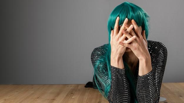 Jonge transgender persoon die groene pruik kopie ruimte draagt