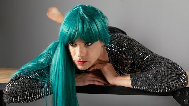 Jonge transgender persoon met groene pruik vooraanzicht