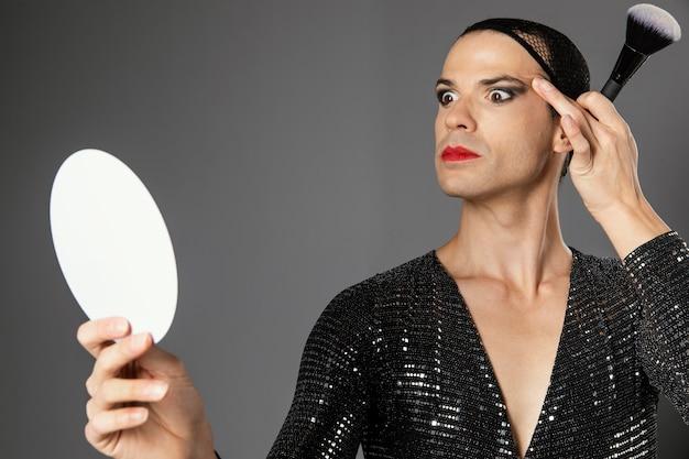 Jonge transgender persoon op zoek naar de spiegel vooraanzicht