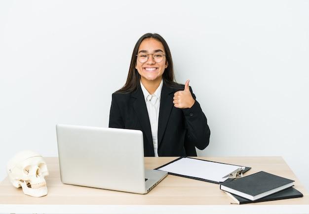 Jonge traumatoloog aziatische vrouw die op witte muur wordt geïsoleerd die en duim glimlacht opheft