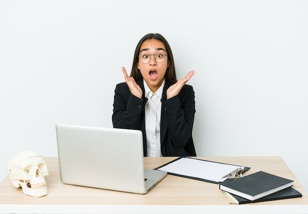 Jonge traumatoloog aziatische vrouw geïsoleerd op een witte muur verrast en geschokt.