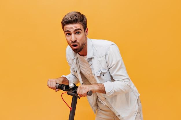 Jonge trendy bebaarde man met blauwe ogen in spijkerjasje en geruit t-shirt op zoek naar camera en poseren met scooter op oranje muur