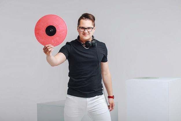 Jonge trendy dj met koptelefoon en vinyl. fan van moderne rockmuziek
