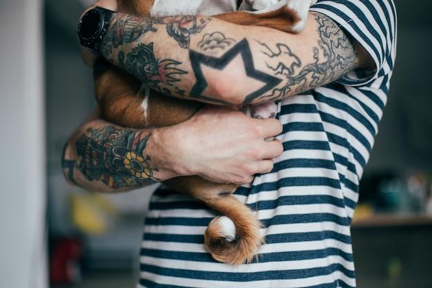 Jonge trendy hipster met gekke krullende tatoeages knuffelt zijn kleine beste vriend