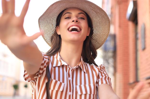 Jonge trendy meid maakt selfie uit handen met telefoon op straat in de zomerstad.