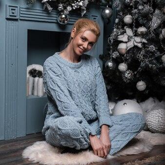 Jonge trendy mooie vrouw in een stijlvolle blauwe gebreide trui zittend op een vloer in een woonkamer in de buurt van een feestelijke kerstboom met vintage speelgoed en ballen