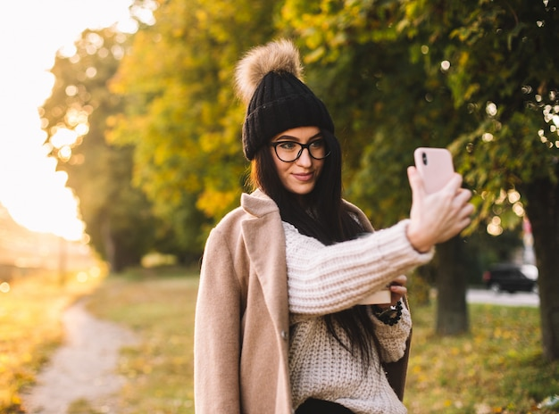 Jonge trendy vrouw blogger met koffie in het park