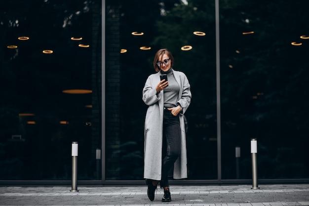 Jonge trendy vrouw in grijze jas praten aan de telefoon