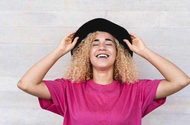 Jonge trendy vrouw lachend buitenshuis terwijl het dragen van stijlvolle hoed - focus op gezicht