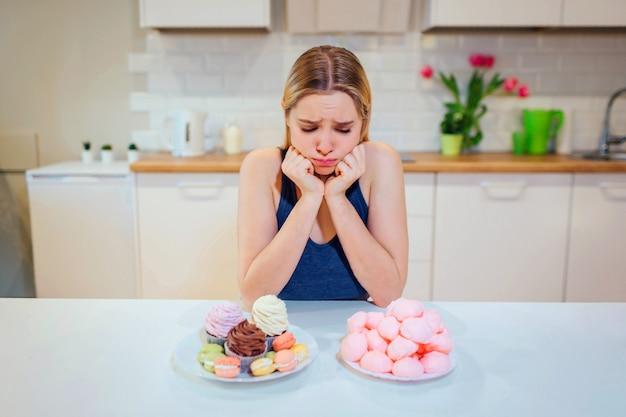 Jonge triest vrouw in blauw t-shirt kiest tussen verse groenten of snoep terwijl ze in de keuken kijken.