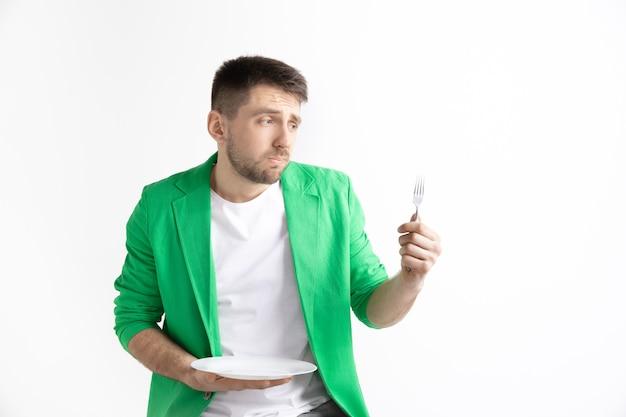 Jonge trieste aantrekkelijke blanke man met lege schotel en vork geïsoleerd op een grijze achtergrond. kopieer de ruimte en maak een mock-up. lege sjabloon achtergrond. afwijzen, afwijzing concept