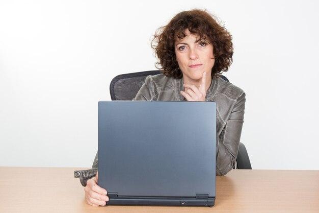 Jonge trieste ernstige vrouw denken, die op laptop werkt