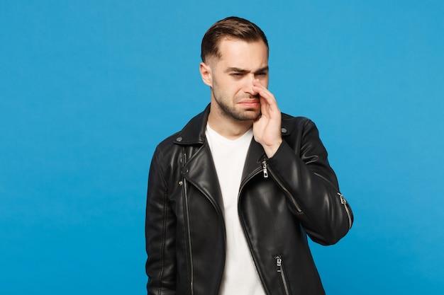 Jonge trieste gefrustreerde bezorgde ongeschoren man in zwarte jas wit t-shirt op zoek camera geïsoleerd op blauwe muur achtergrond studio portret. mensen oprechte emoties levensstijl concept. bespotten kopie ruimte.