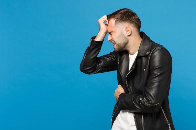 Jonge trieste gefrustreerde bezorgde ongeschoren man in zwarte jas wit t-shirt zet arm op hoofd geïsoleerd op blauwe muur achtergrond studio portret. mensen oprechte emoties levensstijl concept. bespotten kopie ruimte.