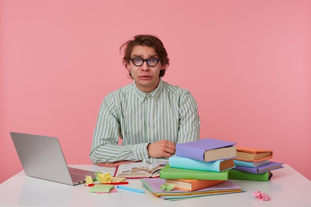 Jonge trieste man met bril, zittend aan een tafel met boeken, werken op een laptop, ziet er ongelukkig uit, draagt een leeg shirt, kijkt naar de camera geïsoleerd op roze achtergrond.