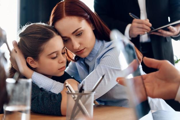 Jonge trieste moeder knuffels dochtertje overstuur.