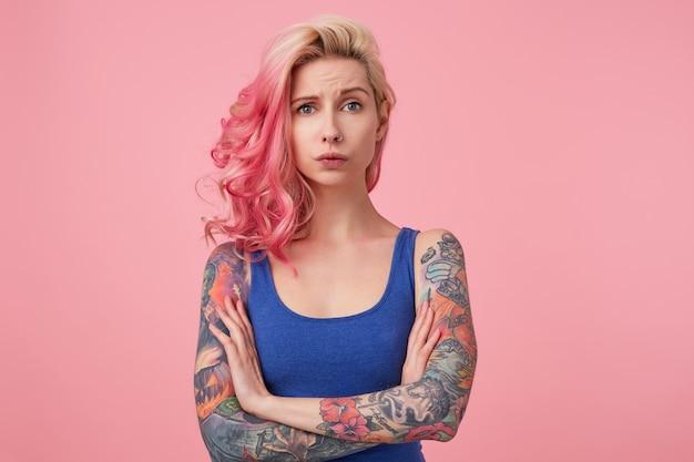 Jonge trieste schoonheid vrouw met roze haar, staat met gekruiste armen, ziet er ontevreden en ongelukkig uit, draagt een blauw shirt. mensen en emoyion concept.