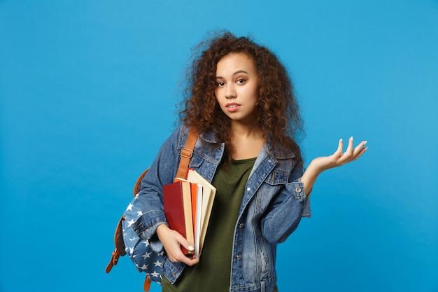 Jonge trieste student in denim kleding en rugzak houdt boeken geïsoleerd op blauwe muur