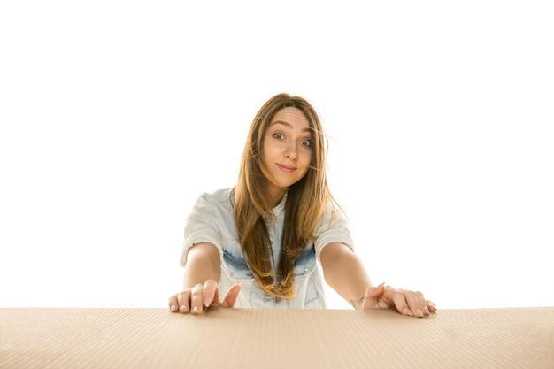 Jonge trieste vrouw die het grootste postpakket opent dat op een witte muur is geïsoleerd