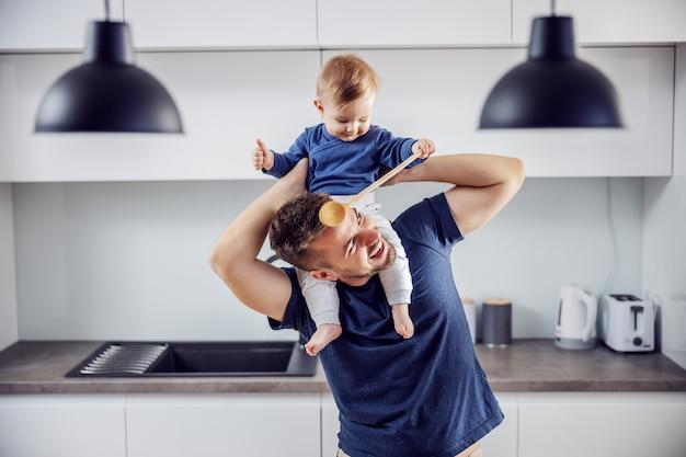 Jonge trotse glimlachende positieve alleenstaande vader die zijn geliefde zoon op schouders houdt en plezier en keuken heeft. peuter bedrijf mengen lepel en spelen met zijn vader.