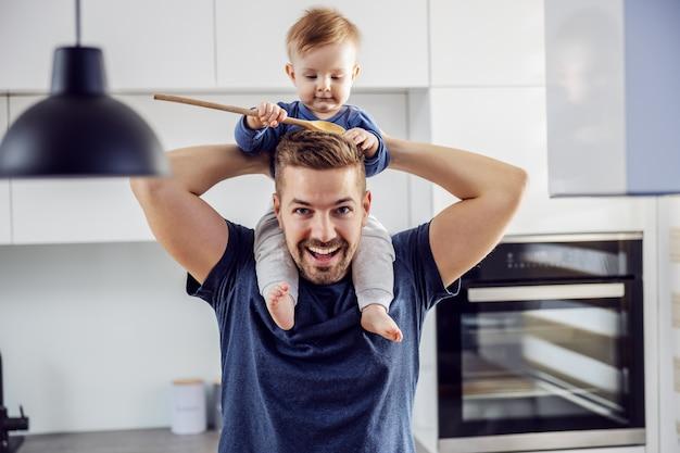 Jonge trotse glimlachende positieve alleenstaande vader die zijn geliefde zoon op schouders houdt en plezier en keuken heeft. peuter mengen lepel houden en ermee spelen.