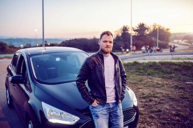 Jonge trotse knappe kaukasische bebaarde blonde man in leren jas leunend op zijn moderne nieuwe auto en poseren met handen in zijn zakken.
