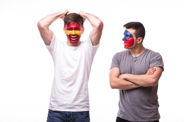 Jonge tsjechische en spaanse voetbalfans die op witte muur worden geïsoleerd