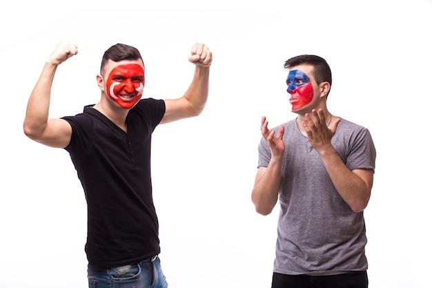 Jonge tsjechische en tunesische voetbalfans winnen en verliezen emoties die op een witte muur worden geïsoleerd