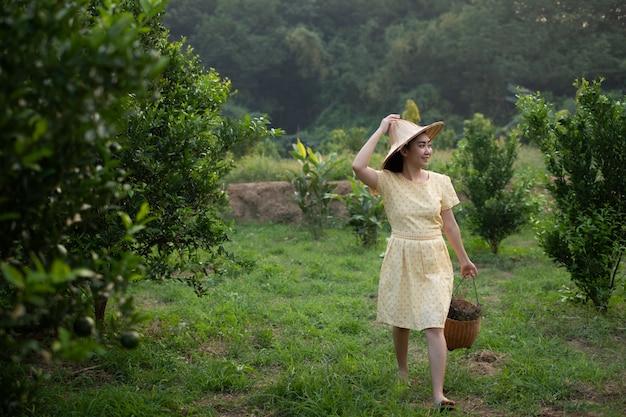 Jonge tuinman aziatische vrouw die en een mand glimlacht draagt