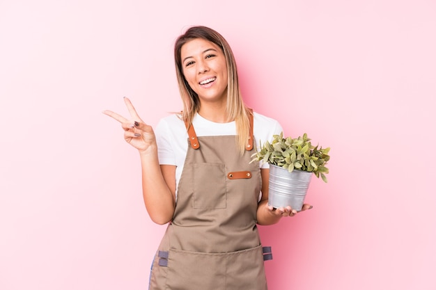 Jonge tuinman blanke vrouw geïsoleerd blij en zorgeloos met een vredessymbool met vingers.