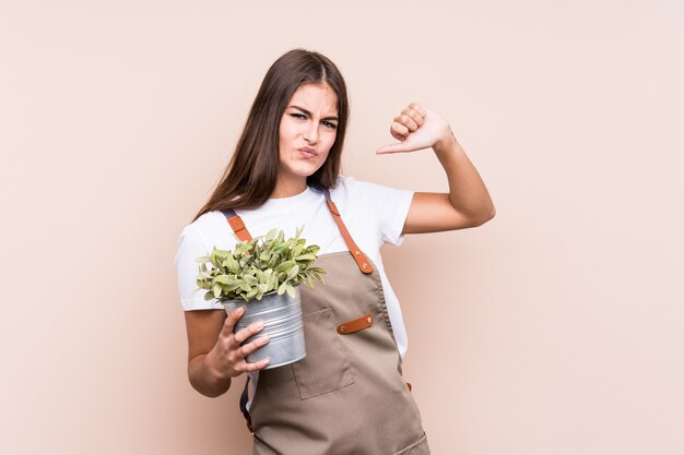Jonge tuinman blanke vrouw met een plant geïsoleerd voelt trots en zelfverzekerd, voorbeeld te volgen.