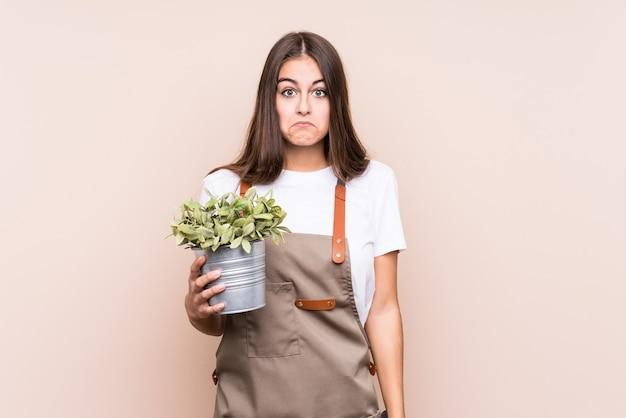 Jonge tuinman blanke vrouw met een plant geïsoleerdhaalt schouders en open ogen verward.